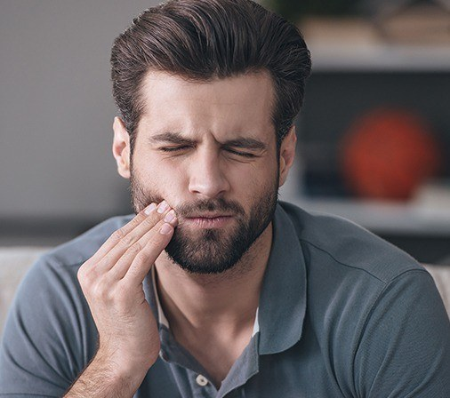Man in pain holding his cheek