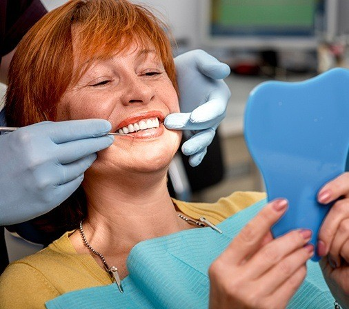 Older woman in dental chair looking at smile